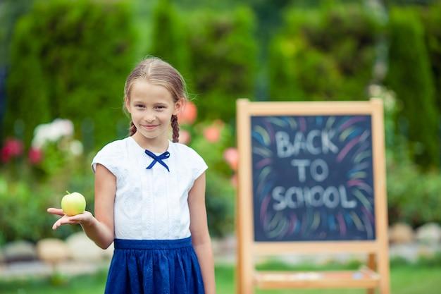 Счастливый маленькая школьница с доске на открытом воздухе