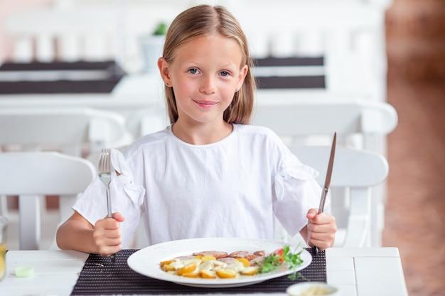 Очаровательная маленькая девочка обедает в кафе на открытом воздухе