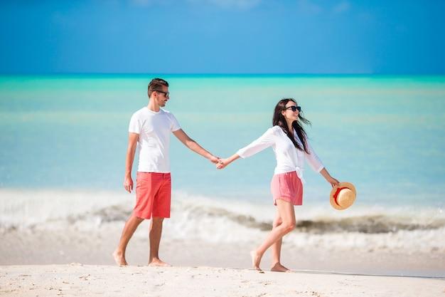 白いビーチで若いカップル。新婚旅行での幸せな家族