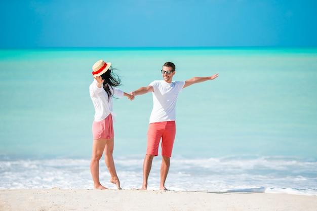 白い砂浜とターコイズブルーの海の水と熱帯のビーチを歩く若いカップル