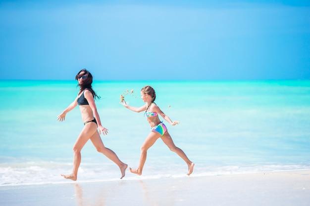 Красивая мама и дочка на карибском пляже весело проводят время вместе