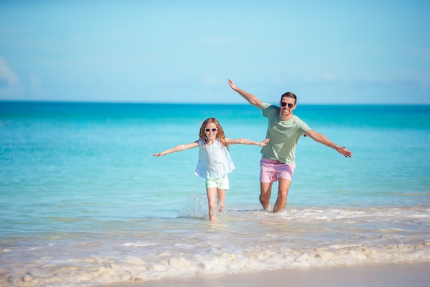 カリブ海のアンティグア島で白い砂浜とターコイズブルーの海の水と熱帯のカーライル湾のビーチで一緒に歩いて熱帯のビーチで家族。