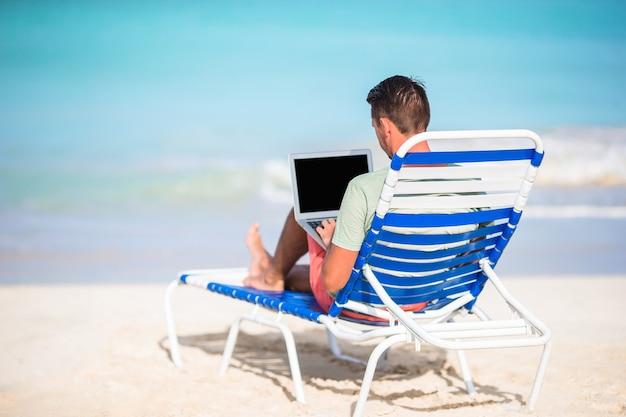 熱帯のビーチのラップトップを持つ若者。コンピューターと長椅子に座っている男