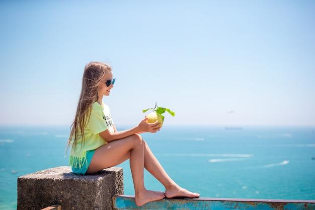 地中海と空の背景に手に大きな黄色いレモン。