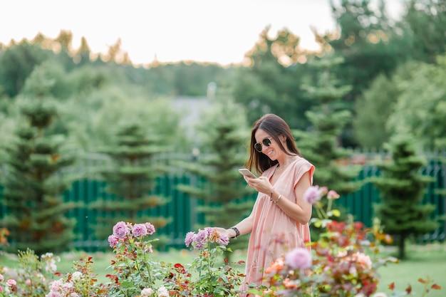 美しいバラの中でフラワーガーデンの少女。バラの香り