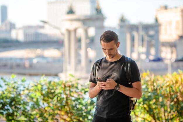 スマートフォンとヨーロッパ通りのバックパックの男観光客。