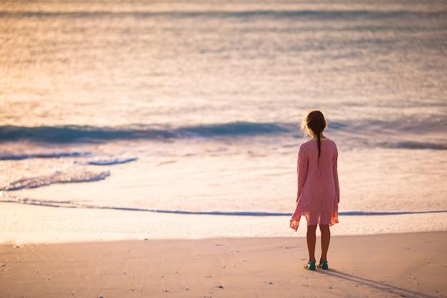 夕暮れ時の白いビーチの上を歩いてかわいい幸せな女の子。