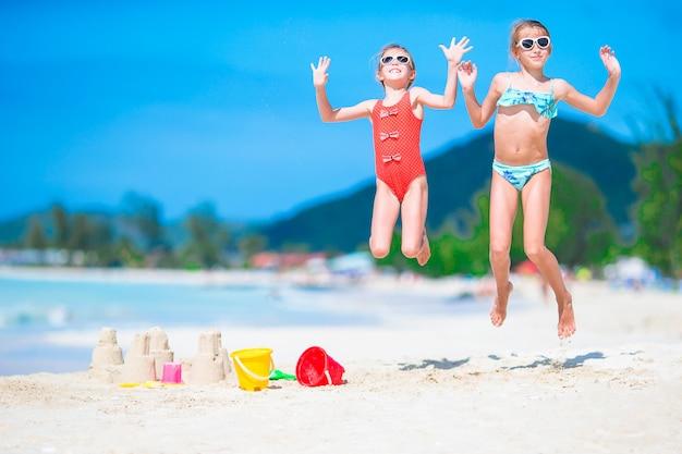 Двое детей делают замок из песка и веселятся на тропическом пляже