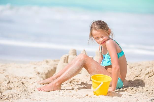 白い熱帯のビーチでビーチおもちゃで遊ぶ愛らしい少女