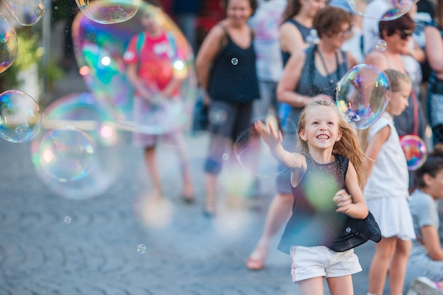 Очаровательная маленькая девочка дует мыльные пузыри в трастевере в риме, италия
