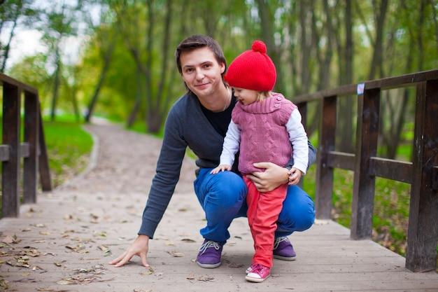 秋の公園でかわいい娘と歩いて若い父親の肖像画