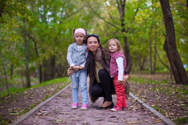 Молодая мама со своими маленькими дочерьми смотрит в камеру на улице