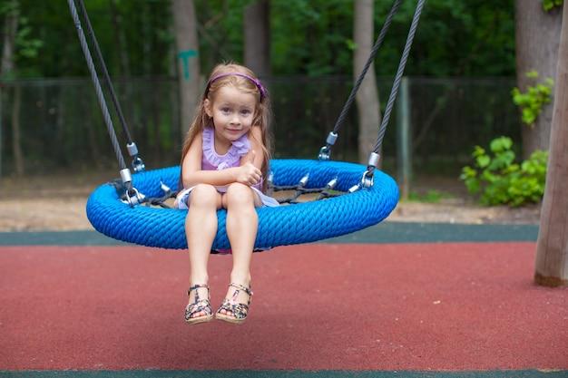 遊園地でスイングの少女