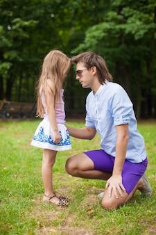 公園でかわいい娘と若い幸せな父は楽しい時を過す