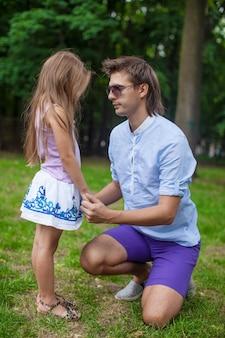 公園でかわいい娘と話している若い幸せな父
