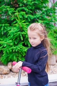 庭のスクーターでのかわいい女の子