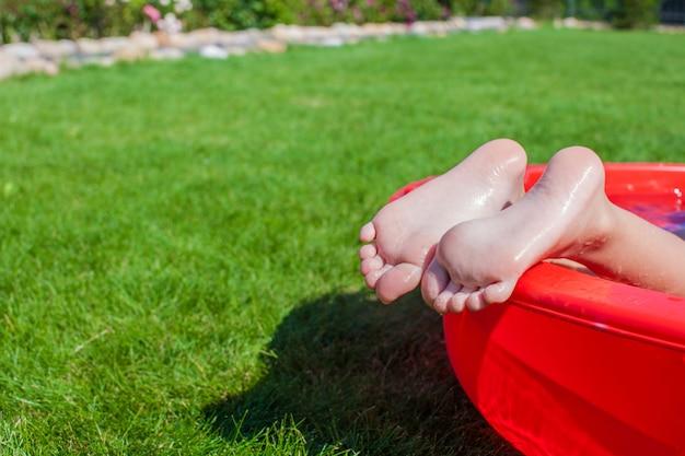 プールで小さな女の子の足のクローズアップ