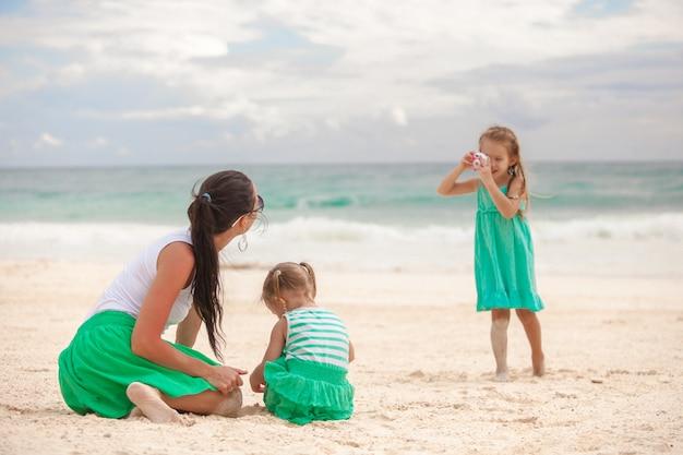 小さな女の子がビーチで妹と母親を撮影します