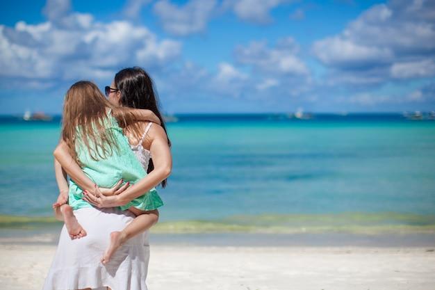 若い母親とかわいい娘の背面図は、エキゾチックなビーチで楽しい時を過す