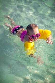 素敵なサングラスで海でダイビングを持つ少女