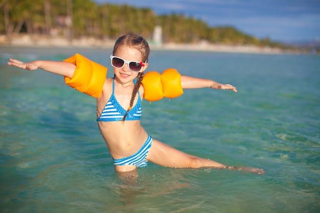 愛らしい少女は、熱帯のビーチでの休暇に海で楽しい時を過す