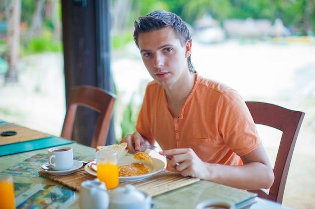 リゾートのレストランで朝食を持っている若い男