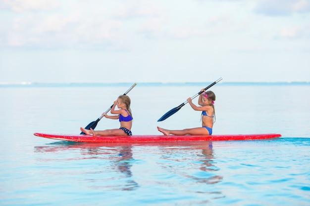 Маленькие девочки плавают на доске для серфинга во время летних каникул