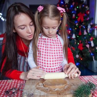 クリスマスのジンジャーブレッドのクッキーを一緒に焼くサンタ帽子で幸せな家族