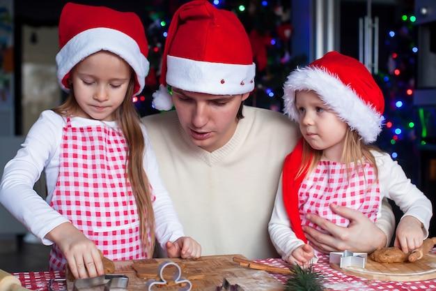 家族が台所でクリスマスジンジャーブレッドクッキーを焼く