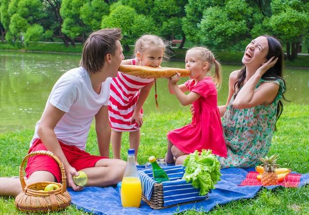 幸せな家族が公園でピクニックし、楽しい時を過す
