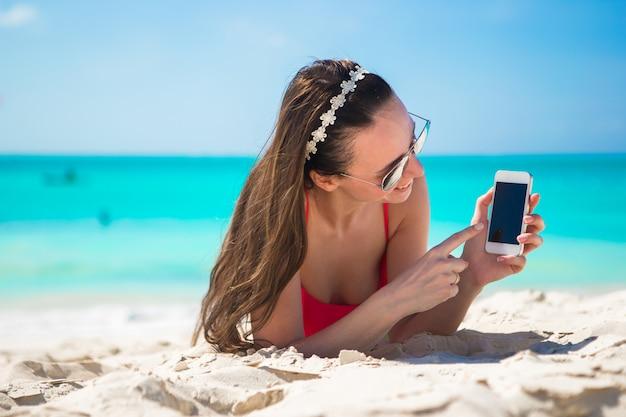 白いビーチに彼女の携帯電話を持つ若い女性