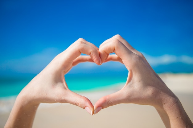 ターコイズブルーの海を背景に手で作られた心