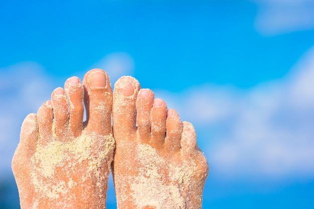 Крупным планом женские ноги на белом песчаном пляже
