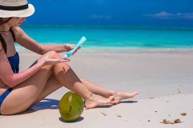 Молодая женщина наносит крем на гладкие загорелые ножки