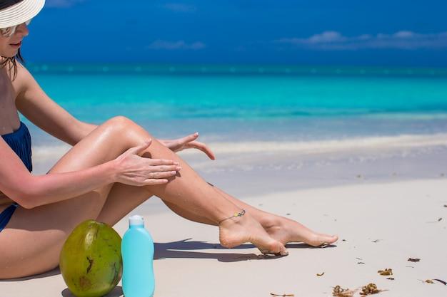 若い女性はビーチで彼女の滑らかな日焼けした足にクリームを適用します