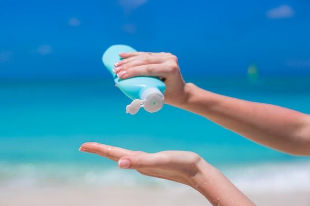 サンクリームボトルから日焼け止めを置く女性の手