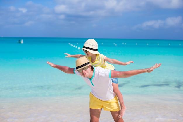 幸せな父と彼の愛らしい小さな娘は、熱帯のビーチで楽しい時を過す