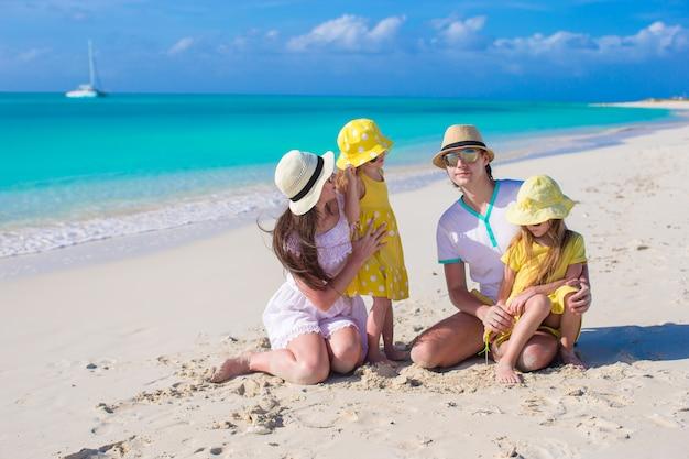 熱帯の休暇中にビーチでポーズをとって幸せな家族