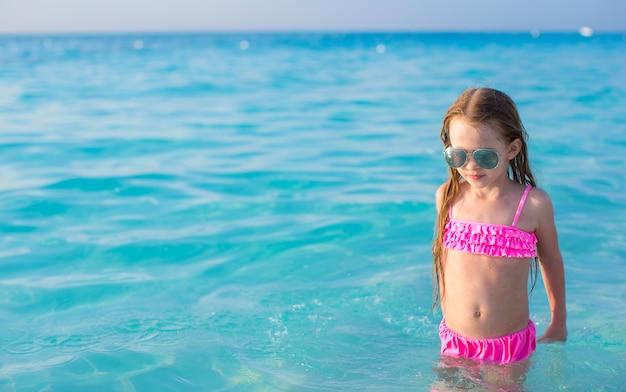 青緑色の水で泳ぐ愛らしい少女