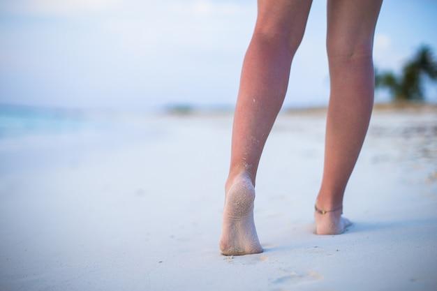 白い砂浜のビーチで男性の足のクローズアップ