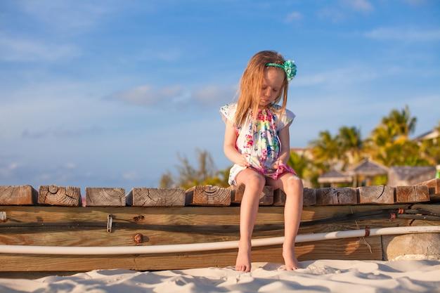 日没の白い熱帯のビーチでのかわいい女の子
