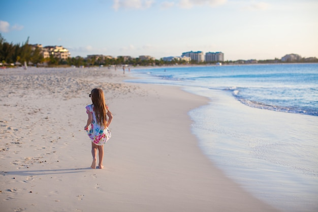 日没の白い熱帯のビーチを歩いてかわいい女の子