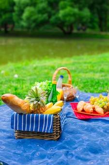 果物、パン、白ワインのボトル付きピクニックバスケット