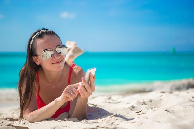 エキゾチックなビーチで彼女の携帯電話を持つ若い女性