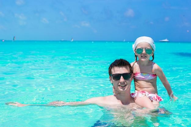 Счастливый отец играет с маленькой дочкой в идеальном море