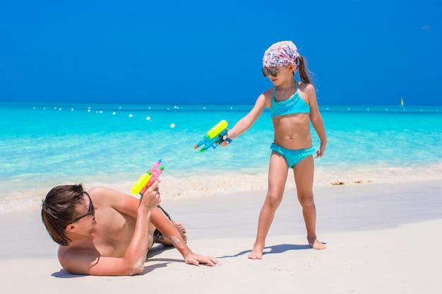 幸せな父と楽しんで熱帯のビーチで彼の愛らしい小さな娘