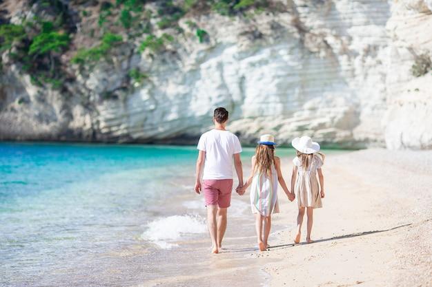 お父さんと白いビーチで子供たちの幸せな美しい家族