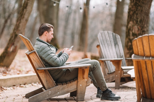 カフェで屋外の携帯電話で白人の観光少年。モバイルスマートフォンを使用している人。