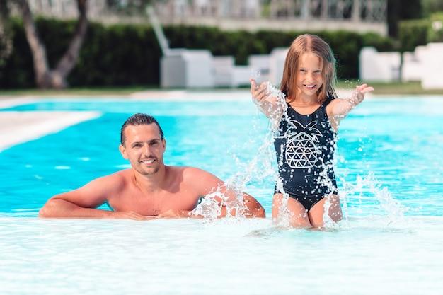 ママと豪華なスイミングプールで夏休みを楽しんでいる小さな娘の家族