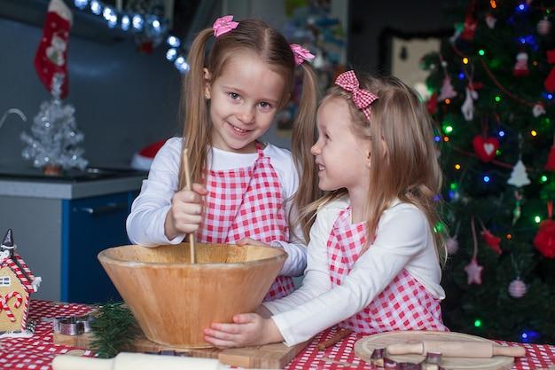 小さなかわいい姉妹がクリスマスのためのジンジャーブレッドクッキーを焼く